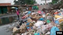 Angola, Luanda. Uma mulher atravessa o amontoado de lixo de galochas calçadas