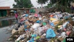 Angola, Luanda. Uma mulher atravessando amontoado de lixo.