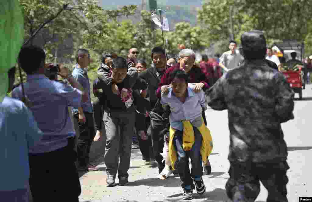 Men carry injured people to an ambulance at Longmen Village, Lushan county, Ya'an, Sichuan province, Apr. 20, 2013.