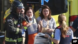 17일 스페인 바르셀로나에서 응급요원들이 차량 돌진 테러로 부상한 희생자들을 부축하고 있다.