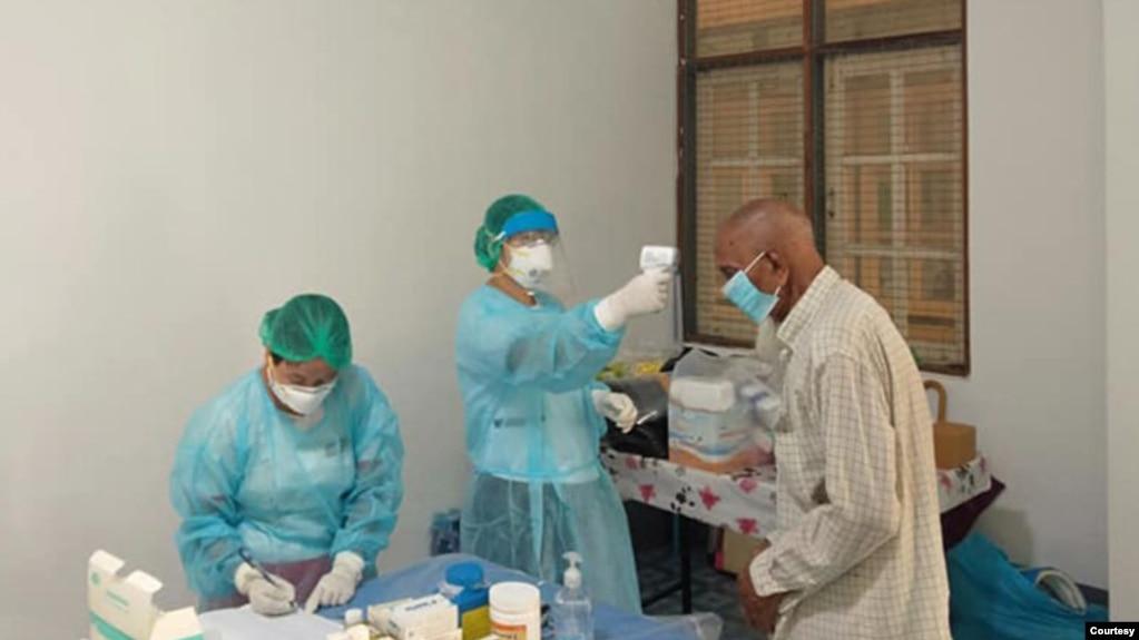 သဃၤန္းကၽြန္းၿမိဳ႕နယ္တြင္ ဖြင့္လွစ္ထားသည့္ ဖ်ားနာလူနာေဆးကုခန္းတြင္ ကုသေပးေနသည့္ ျမင္ကြင္း။ (ဧၿပီ ၁၁၊ ၂၀၂၀။ ဓာတ္ပုံ - Dr Kyaw Swar Oo Facebook)