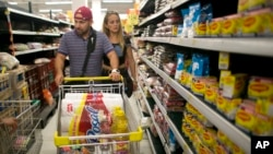 Venezuelan husband and wife Ramiro Ramirez and Tebie Gonzalez shop for food in Cucuta, Colombia, July 17, 2016, during the temporary opening of the border. U.S. firms doing business in Venezuela are adjusting accounting techniques.