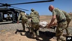 Грузинские военнослужащие из международного контингента в Афганистане эвакуируют раненного афганского солдата. Провинция Гельменд. 6 мая 2011 г.