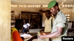 A Togolese soldier has his identity checked before casting his ballot during the early voting for the country's parliamentary elections, at the RIT camp in Lome, July 22, 2013.