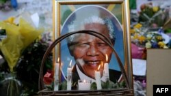 FILE - Candles are seen burning by a portrait of Nelson Mandela outside of the Mediclinic Heart Hospital in Pretoria, South Africa, where he was in critical condition, July 6, 2013.