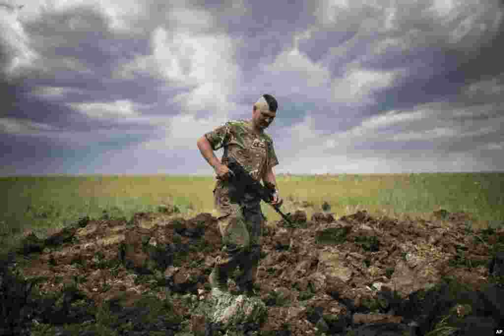 A Ukrainian serviceman investigates a crater left by a Grad rocket in the village of Toshkivka, Luhansk region, eastern Ukraine.