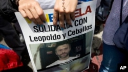 A supporter of jailed opposition leader Leopoldo Lopez holds a poster showing his face during an anti-government protest in Caracas, Venezuela, May 30, 2015.