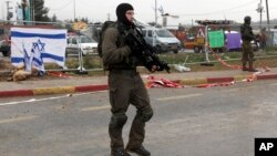 FILE - Israeli soldiers stand at the scene of an alleged stabbing attempt at Gush Etzion junction in the West Bank, Dec. 1, 2015. Near-daily violence has left more than 20 Israelis dead in the past three months.