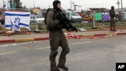 Israeli soldiers stand at the scene of an alleged stabbing attempt at Gush Etzion junction in the West Bank, Dec. 1, 2015.
