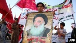 Một người đàn ông Iraq đem theo bức chân dung Đại giáo sĩ Ayatollah Ali al-Sistani, lãnh đạo tinh thần của người Shia, khi người dân tập trung bày tỏ quyết tâm xin tham gia lực lượng an ninh Iraq trong cuộc chiến chống các phần tử chủ chiến Jihad, 19/6/2014