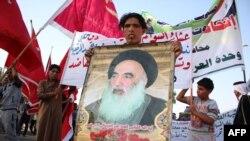 Seorang pria Irak membawa poster bergambar Ulama Syiah Ayatollah Ali al-Sistani saat berkumpul untuk bergabung dengan pasukan keamanan Irak untuk melawan militan (19/6). (AFP/Haidar Mohammed Ali)