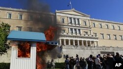 A Presidential guard box set alight by protesters at the unknown soldier monument burns during clashes outside the Greek Parliament, October 19, 2011.