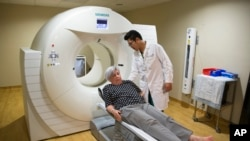 Judith Chase Gilbert, of Virginia., is loaded into PET scan machine by nuclear medicine technologist J.R. Aguilar as part of a study on Alzheimer's disease at Georgetown University Hospital, on Tuesday, May 19, 2015, in Washington, DC. (AP Photo/Evan Vucci)