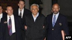 Tổng Giám đốc IMF Dominique Strauss-Kahn (giữa) bị còng và áp tải ra khỏi Trụ sở cảnh sát ở New York ngày 15 /5/2011