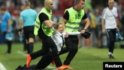 俄羅斯女性主義朋克樂隊Pussy Riot (暴動小貓)成員在世界盃決賽時闖入球場被警察拖走(2018年7月15日)