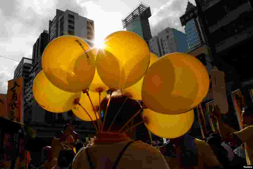 A protester carries yellow balloons featuring umbrellas, symbol of the Occupy Central movement, during a protest march on the day marking the 19th anniversary of Hong Kong's handover to Chinese sovereignty from British rule, in Hong Kong, China.