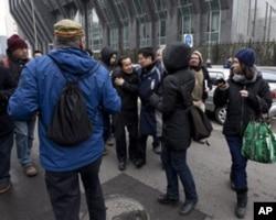 穿着便衣的安全人员试图把跟记者讲话的倪玉兰律师程海(面对镜头者)推走。
