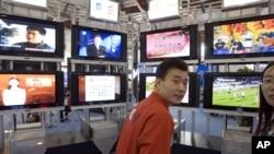 资料照:在2006年北京国际广播电影电视设备展上,一位男士站在一系列电视机前。