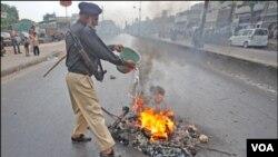 Seorang polisi Pakistan berusaha memadamkan api dalam kerusuhan di Karachi (1/8).