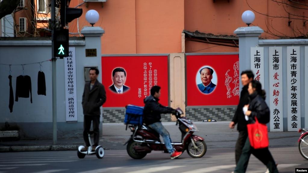 上海市民在张贴着中共领导人习近平和前领导人毛泽东的宣传画前走过。(资料照片)