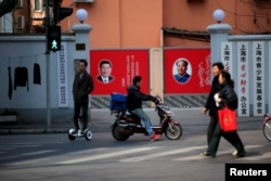 FILE - People cross a street in front of posters depicting late Chairman Mao Zedong (R) and China's President Xi Jinping in Shanghai, China, March 1, 2016.