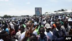 Les partisans d'Henri Konan Bedie, tenant le portrait de l'ancien président ivoirien et actuel dirigeant du Parti démocratique ivoirien (PDCI) ,lors d'un rassemblement électoral le 19 octobre 2019 à Yamoussoukro, dans le centre de la Côte d'Ivoire. (Photo par SIA KAMBOU / AFP)