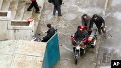 지난 2005년 11월 북한 평양에서 망가진 오토바이를 밀고 가는 주민들의 모습이 서방 기자들의 카메라에 잡혔다.