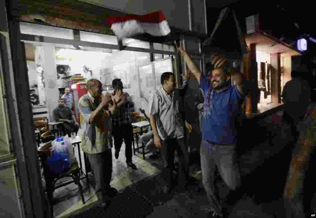 Người Ai Cập ăn mừng tin tổng thống Mohamed Morsi bị lật đổ trong một quán trà ở khu vực Zamalek ở Cairo. Tổng tư lệnh quân đội Ai Cập đã loan báo đình chỉ bản hiến pháp do phe Hồi giáo hậu thuẫn và kêu gọi bầu cử sớm.