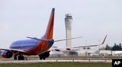FILE - A Southwest Airlines jet waiting to depart in view of the air traffic control tower at Seattle-Tacoma International Airport, April 23, 2013.