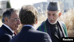 Afghanistan President Hamid Karzai (R) walks alongside U.S. Defense Secretary Leon Panetta (L) on a guided tour of the Pentagon Memorial, in memory of the victims of the September 11 attack, at the Pentagon, January 10, 2013.