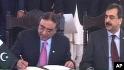 Pakistan's President Asif Ali Zardari, left, signs a constitutional reforms law as Prime Minister Yousuf Raza Gilani looks on during a ceremony in Islamabad, 19 Apr 2010