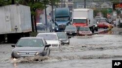 Vehículos pasan en las inundaciones, el viernes 5 de mayo de 2017, en Newark, N.J. Las fuertes lluvias causaron que el agua tapara algunas vías en la ciudad de Nueva York y generaron retrasos de vuelos.