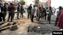 Security officials assess the scene of a bomb blast that killed four people by suspected members of Nigerian Islamist sect Boko Haram in Nigeria's northern city of Kaduna, April 8, 2012.