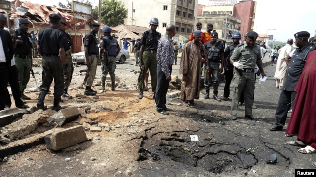 Security officials assess the scene of a suspected Boko Haram bomb attack that killed four people in Nigeria's northern city of Kaduna, April 8, 2012.