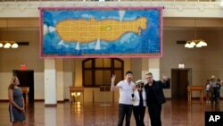 Bono, right, and The Edge, left, of the Irish rock band U2, flank Yoko Ono, the widow of John Lennon, at the unveiling of a giant tapestry depicting the island of Manhattan as a yellow submarine piloted by a waving Lennon at Ellis Island, July 29, 2015,