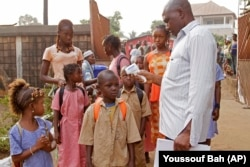 A health care worker takes the temperatures of school children for signs of the Ebola virus in Conakry, Guinea
