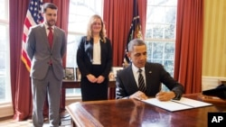 "FILE - President Barack Obama signs an Executive Order, entitled ""Planning for Sustainability in the Next Decade,"" which will cut the Federal Government's greenhouse gas (GHG) emissions over the next decade, March 19, 2015. Behind the president is Senior Adviser Brian Deese and Kate Brandt, Federal Chief Sustainability Officer."