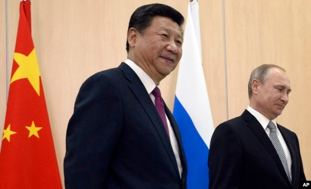 FILE - Russian President Vladimir Putin, right, and Chinese President Xi Jinping smile prior their talks during the summit in Ufa, Russia, July 8, 2015.