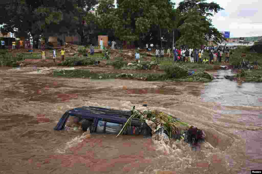 People look at a SUV submerged in floodwaters in Bamako, Mali. Torrential rains provoked flash floods, washing away homes in several neighbourhoods, a government minister said.