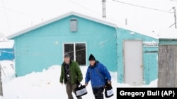 Census bureau director Steven Dillingham, right, walks alongside Census worker Tim Metzger after conducting the first enumeration of the 2020 Census Tuesday, Jan. 21, 2020, in Toksook Bay, Alaska.