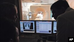 A medical team at Baptist Cardiac & Vascular Institute in Miami, Florida analyze CT scan images on January 30, 2007. (AP Photo/David Adame)