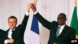Le président sénégalais Macky Sall (à gauche) et le président français Emmanuel Macron (à droite) se tiennent la main après le discours de Macron à Saint-Louis, au Sénégal, le 3 février 2018.