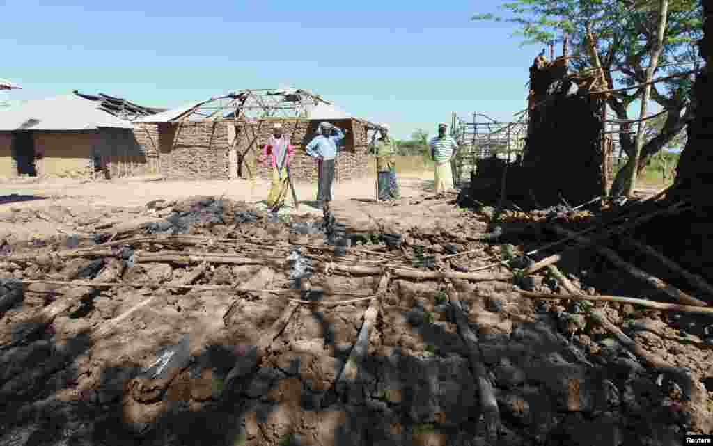 Residents look at a house that was destroyed when their village was attacked, Nduru village in the Tana Delta region of Kenya, January 9, 2013.