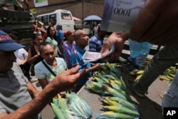 Customers pay with new bank notes for their groceries, at a market in Caracas, Venezuela, Sept. 23, 2017.
