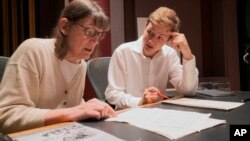 "Professor Patricia Hall and graduate student Joshua Devries review the music manuscript for ""The Most Beautiful Time of Life"" at the Duderstadt Center recording studio on campus in Ann Arbor, Mich. (Christopher Boyes/University of Michigan via AP)"