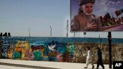 Dua orang pria Afghanistan berjalan melewati papan reklame pemilihan presiden yang menampilkan sosok capres Ashraf Ghani Ahmadza di pusat kota Kandahar, Afghanistan (31/3). Para pejabat Afghanistan mengatakan Taliban telah menculik seorang kandidat pemilihan provinsi di Afghanistan utara, Senin (31/3).