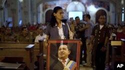 Žena sa slikom venecuelanskog predsednika Uga Čaveza donosi njegovu sliku na misu u jednoj crkvi u Havani, na Kubi