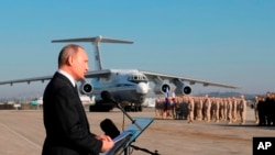 FILE - Russian President Vladimir Putin addresses the troops at the Hemeimeem air base in Syria, Dec. 12, 2017. U.S. President Donald Trump recently shocked advisers in declaring an intention to withdraw troops from Syria. Now, apparently angered by a suspected chemical attack, Trump is threatening imminent military strikes against the Syrian government forces he blames and rattling a saber at Syria's patron, Russia.
