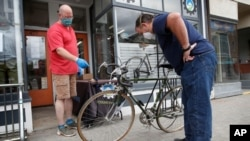 In this June 9, 2020 photo, Harvey Curtis, left, discusses repair plans with customer Jack Matheson outside Sidecountry Sports, a bike shop in Rockland, Maine.