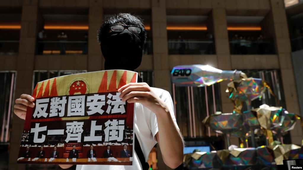 香港一名抗议者举牌反对港版国安法,号召七一游行。(2020年6月30日)